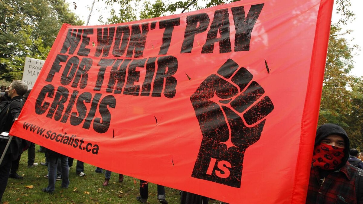 Protesters rally with placards in Toronto's St. James Park during Occupy protests on October 15, 2011.