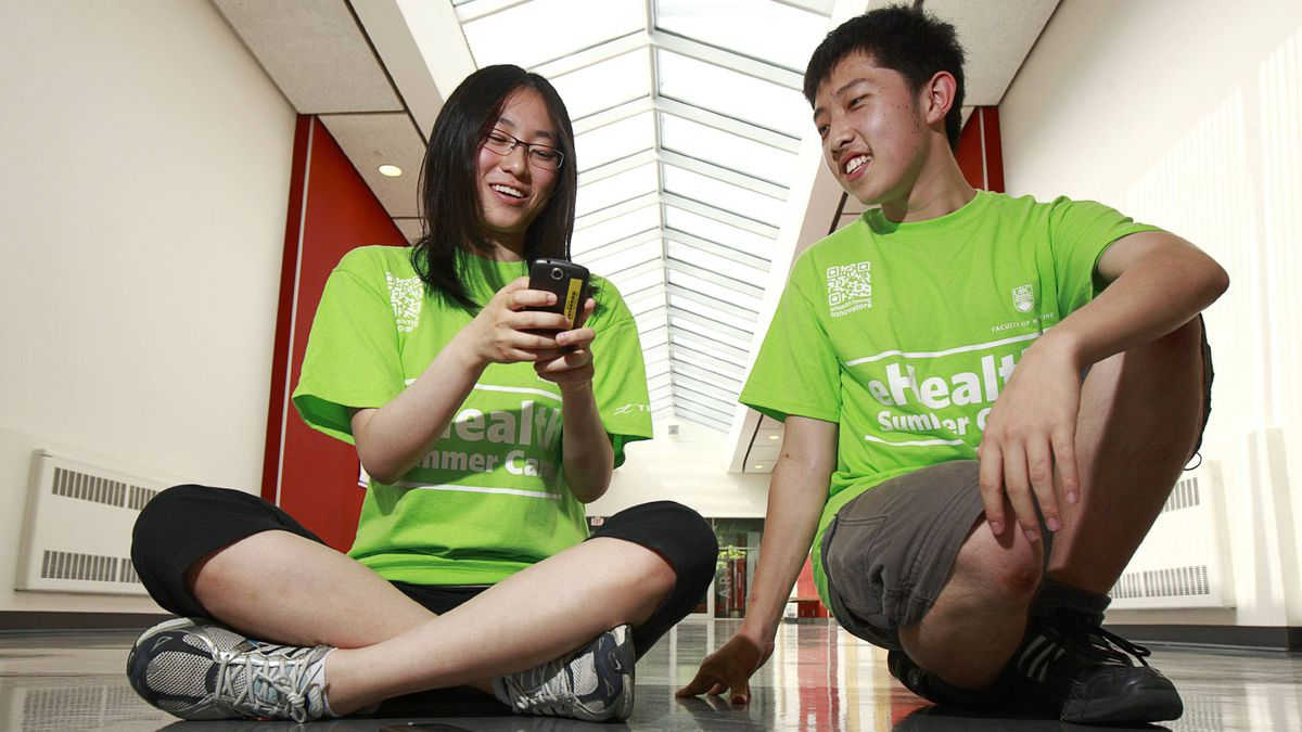 Ainslee Chen and Harvey Zhang try out the medical science apps they developed during a week-long summer camp at the University of British Columbia.