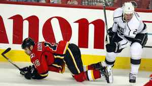The Los Angeles Kings' Matt Grenne knocks the Calgary Flames Tom Kostopoulos to the ice in Calgary.