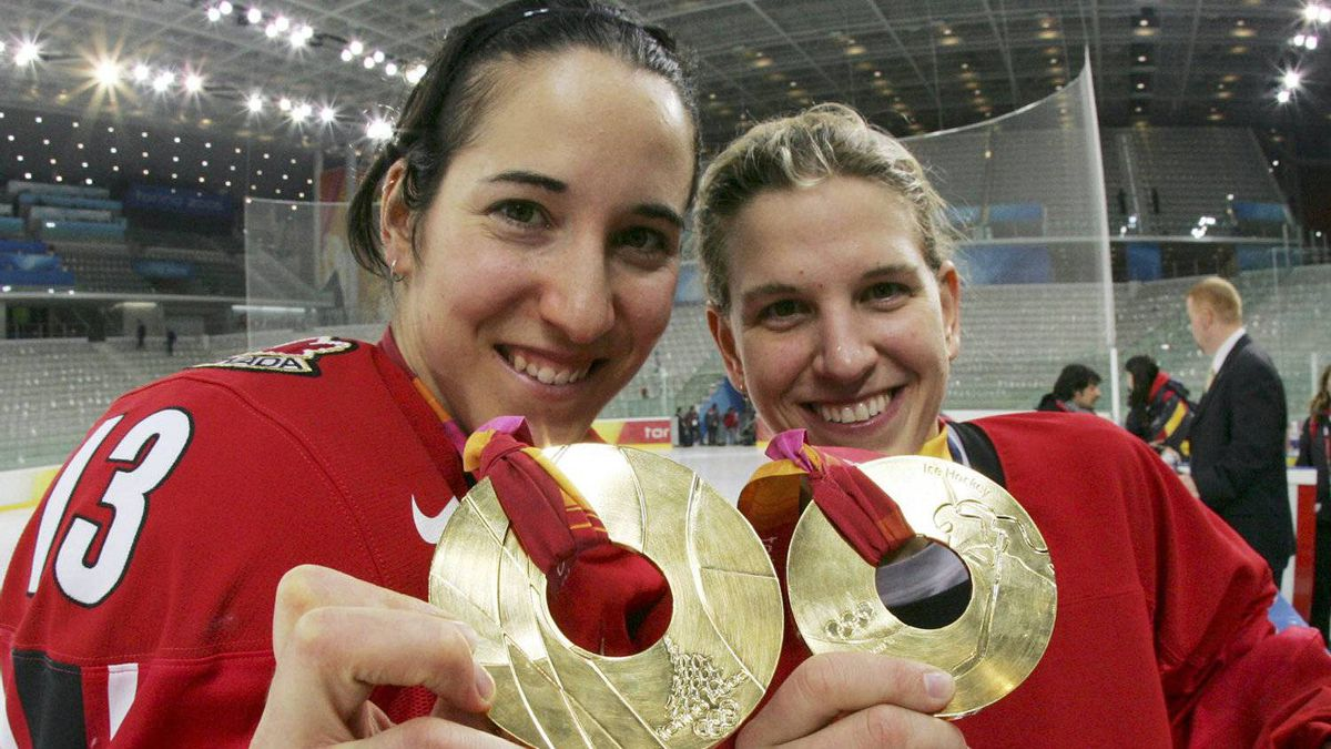 Canada's Caroline Ouellette, left, and goalie Kim St. Pierre celebrate with her gold medal on the ice with champagne after they beat Sweden 4-1 in the Winter Olympics women's ice hockey gold medal game Monday, Feb. 20, 2006, in Turin, Italy. Ouellette was one of four Olympians the NHL has brought in to take part in a fan festival on women's hockey. (AP Photo/Gene J. Puskar)