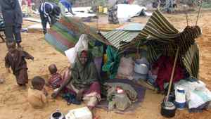 A woman and her children displaced by drought from southern Somalia sit in an open area in a makeshift shelter in a refugee camp in Mogadishu, Somalia, on Wednesday, July 13, 2011.
