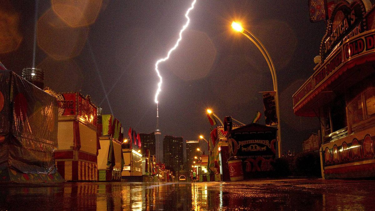 Lightning hits the CN Tower behind the deserted exhibitions grounds in Toronto on Wednesday August 24, 2011. The annual fair was closed due to severe weather.