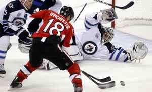 Ottawa Senators' Jesse Winchester (C) is denied a scoring chance by Winnipeg Jets' Mark Stuart and goalie Ondrej Pavelec during the second period of their NHL hockey game in Ottawa October 20, 2011.