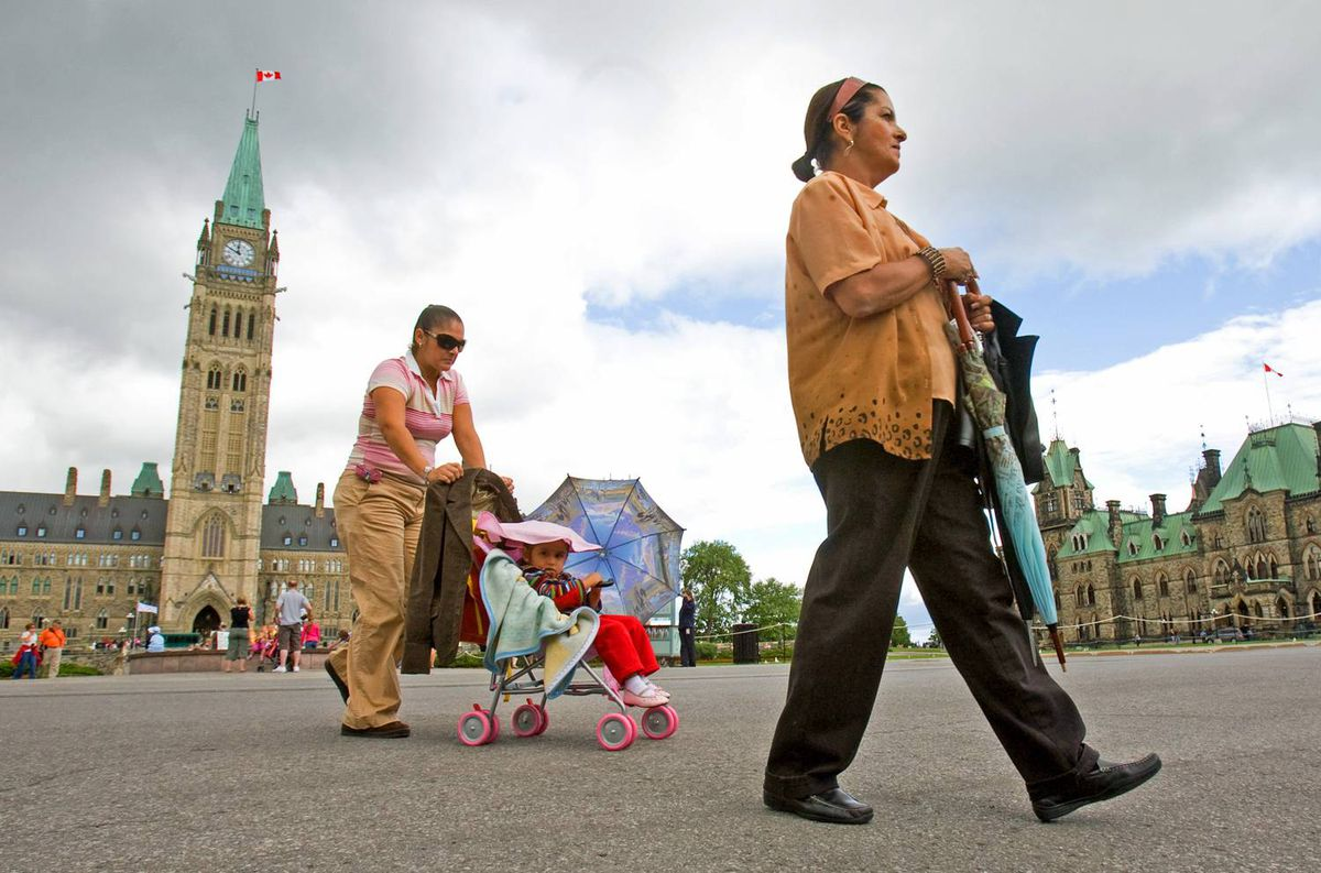 Miriam Llorete, a Mexican tourist, pushes her daughter as she follows her mother during a visit to Parliament Hill on July 14, 2009.