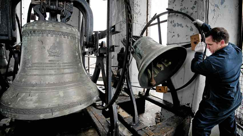 Bell repairman Daniel Desormiers examines the clapper on one of the bells at Notre Dame des Sept Douleurs church in Montreal on Dec. 14.