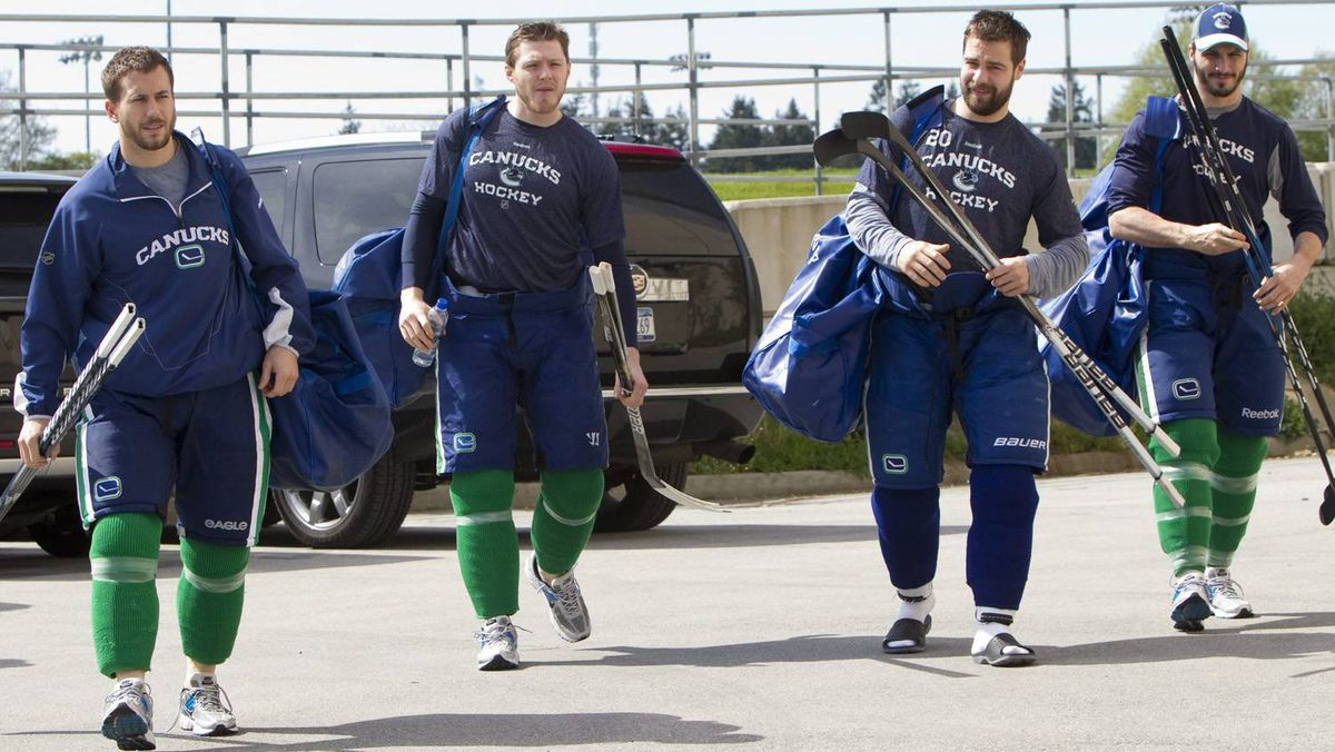 Vancouver Canucks, from left, Jeff Tambellini, Victor Oreskovich, Chris Higgins and Maxim Lapierre arrive for a team practice at the UBC Thunderbird Arena in Vancouver, B.C., Tuesday.