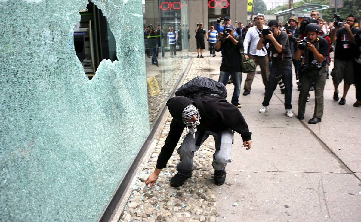 G20 summit protesters smash the window of a business front on Queen Street West near Bay Street in downtown Toronto on Saturday, June 26, 2010. THE CANADIAN PRESS/Chris Young