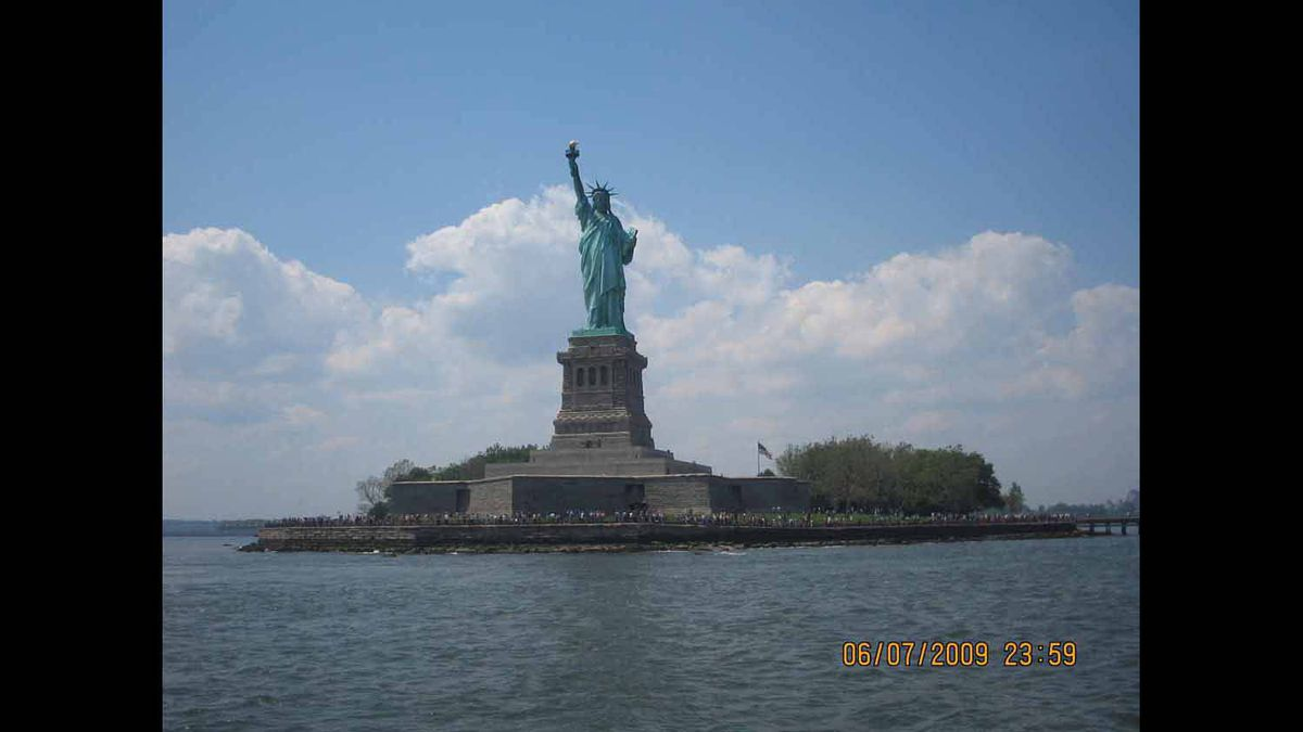 situated in an island accessible by ferry is one of the most admired statues in the world for over 125 years.