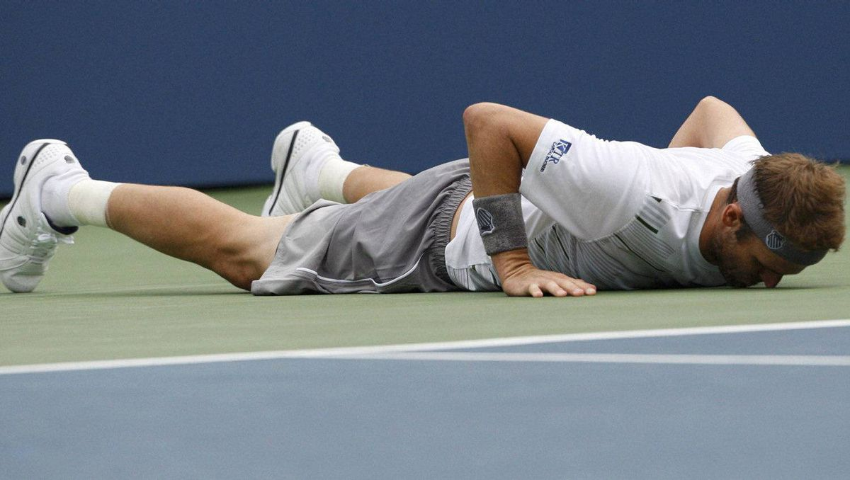 Mardy Fish of the U.S. lies on the court after slipping while returning a shot to Jo-Wilfried Tsonga of France during their match at the U.S. Open tennis tournament in New York, September 5, 2011. REUTERS/Eduardo Munoz