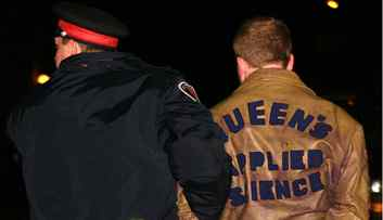 A police officer escorts a reveller at the 2007 Queen's homecoming party, in Kingston, Ont.