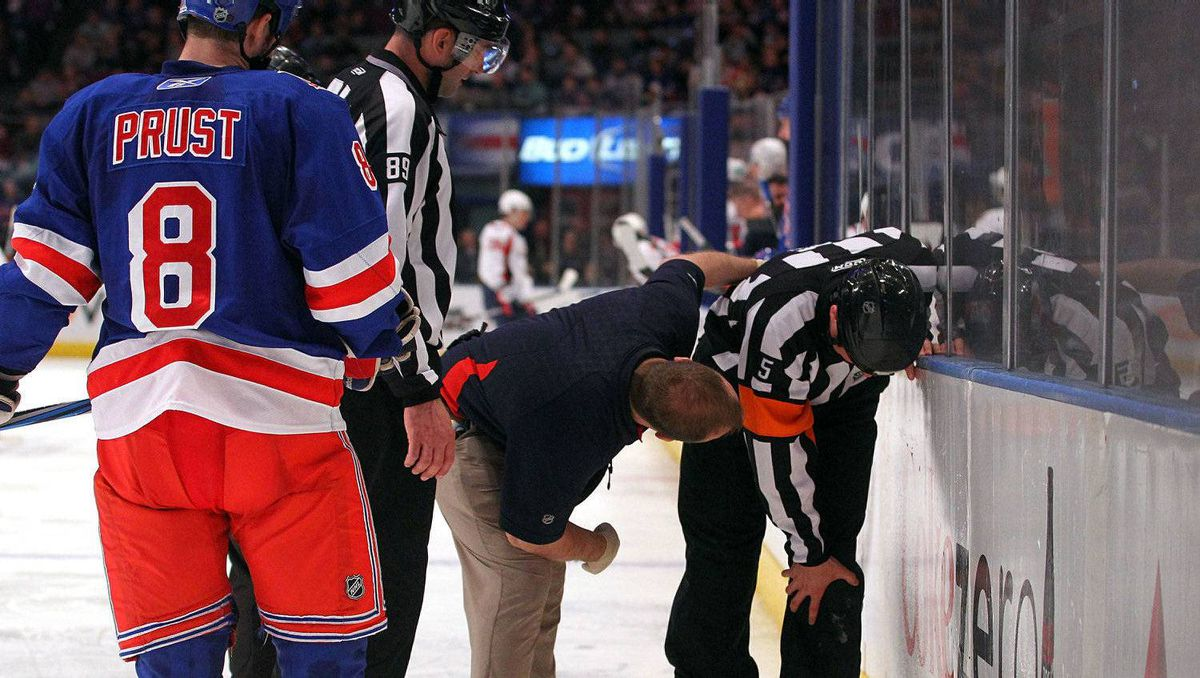 Referee Chris Rooney #5 is tended to as he grabs his leg after he was injured while officiating the game between the New York Rangers and the Washington Capitals. Rooney broke his left-fibula on the play. (Photo by Bruce Bennett/Getty Images)