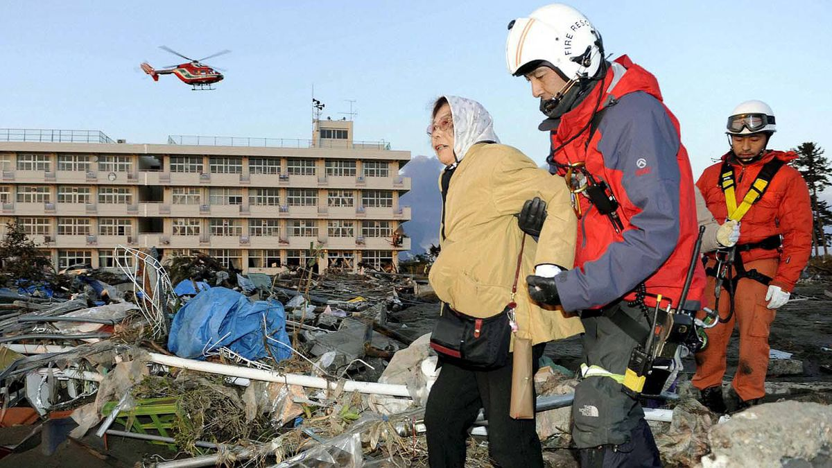 An elderly woman is assisted by rescue personnel in Sendai, in northeastern Japan March 12, 2011.