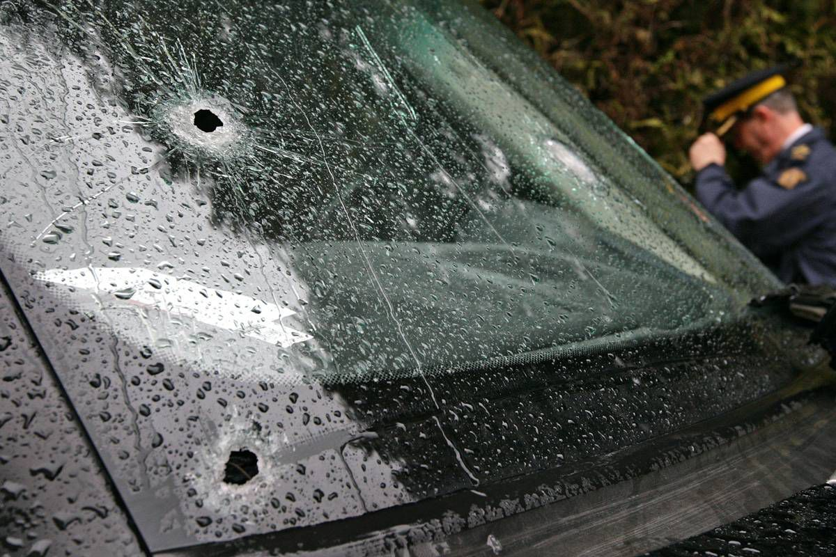 An RCMP officer passes a bullet-riddled vehicle that was involved in a targeted gang shooting on February 16, 2009 in Surrey, B.C., on display outside RCMP headquarters in Vancouver, B.C.