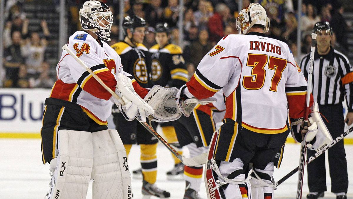 Calgary Flames goalie Miikka Kiprusoff, left, replaces goalie Leland Irving during the second period against the Boston Bruins