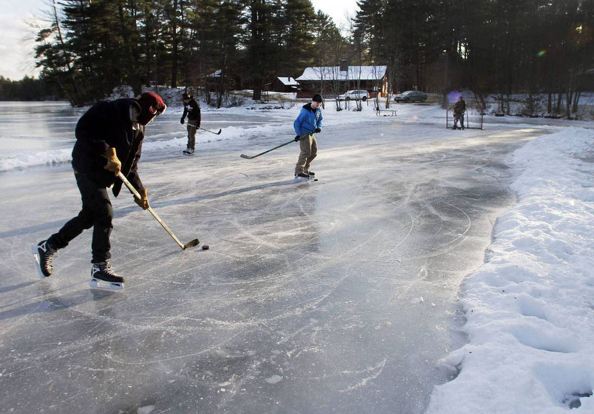Hockey players, from left, Colin Wilkey, Robert Keilig, and brothers Cameron and Jonathan Durling play hockey on Kimball Pond in Hopkinton, N.H.