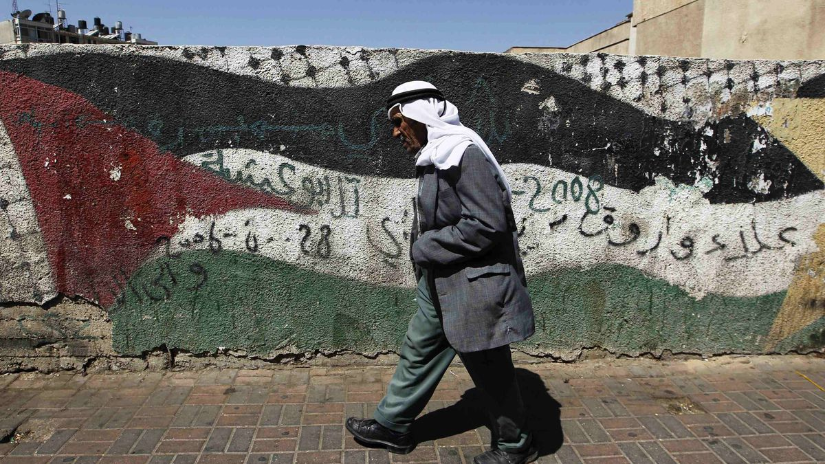 A Palestinian walks past a Palestinian flag painted on a wall in West Bank city of Ramallah Sept.19, 2011.