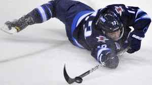 Winnipeg Jets' Kyle Wellwood makes a pass while falling to the ice against the Colorado Avalanche during the third period of their NHL hockey game in Winnipeg February 19, 2012. REUTERS/Fred Greenslade