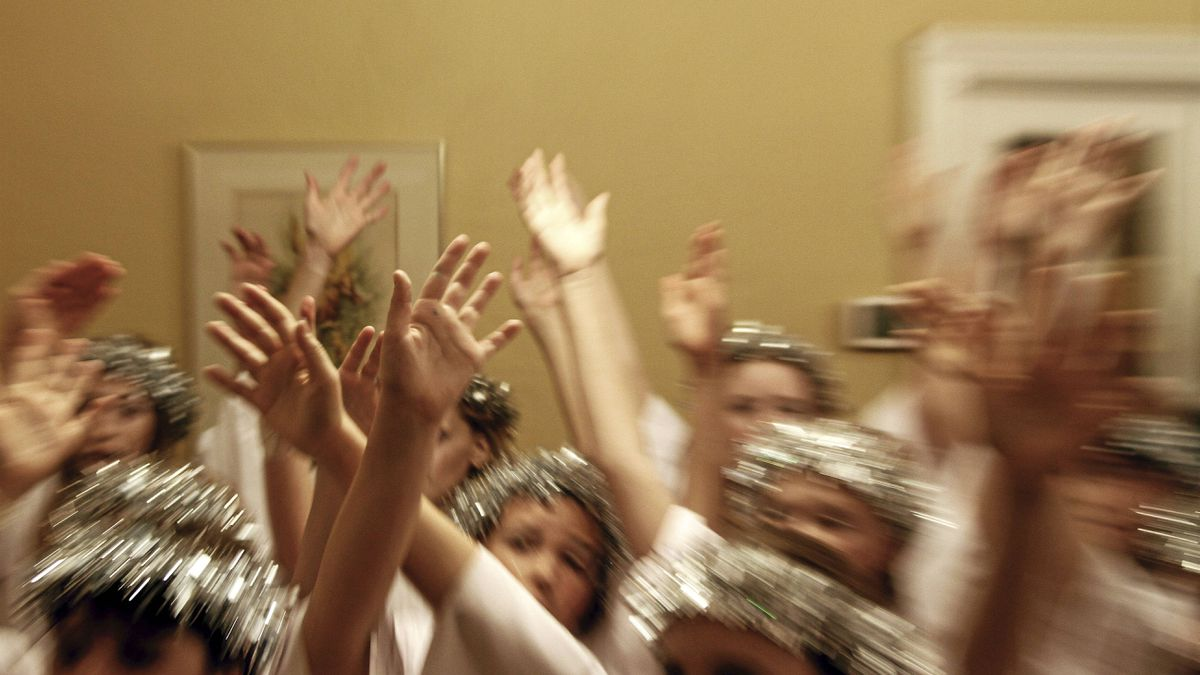 In a backroom, the angel choir gathers to warm up their vocal chords with a last-minute run-through.