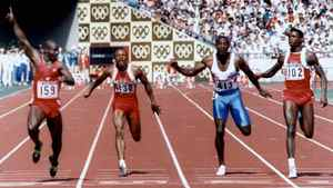 Ben Johnson signals victory as he wins the men's 100 metres final to take the gold medal over American Carl Lewis, far right, at the Seoul Olympic Games.