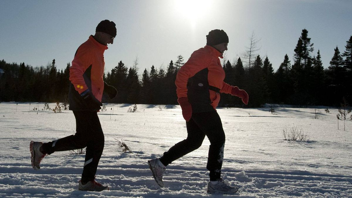 Bill Anderson, left, and Gail Teed run along a snowmobile trail in Rothesay, NB on Thursday, February 17, 2011