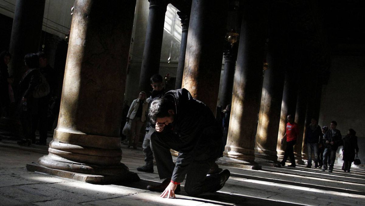 A worshipper prays in the Church of Nativity, the site widely believed to be the birthplace of Jesus Christ, in the West Bank city of Bethlehem, on December 24, 2011, as Christians gather for Christmas mass.