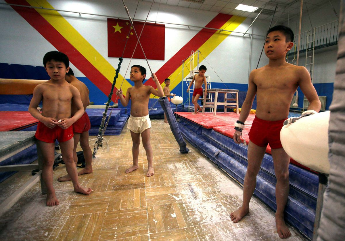 Young gymnasts wait for their turn on various apparatus during a gymnastics class.