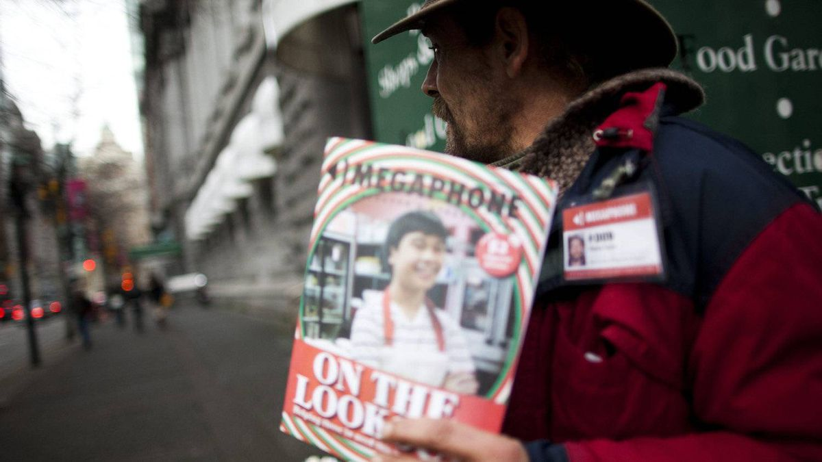 Patrick Doyle sells copies of the Megaphone magazine, a publication that focuses on the Downtown Eastside, at the corner of West Hastings Street and Granville Street in Vancouver, British Columbia, Thursday, December 15, 2011.