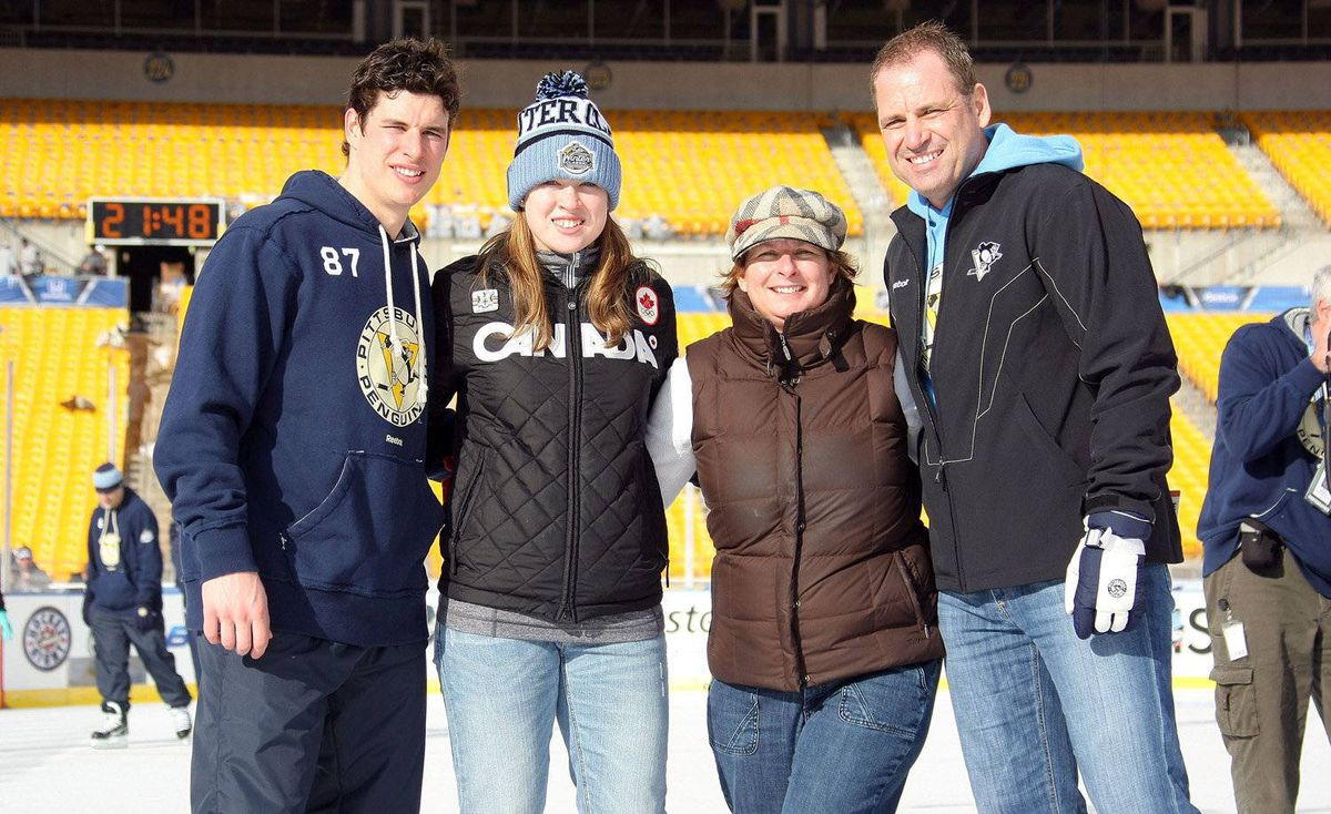 Sidney Crosby #87 of the Pittsburgh Penguins poses for a photo with his father Troy, mother Trina and sister Taylor during a family skate following practice for the 2011 NHL Bridgestone Winter Classic at Heinz Field on December 31, 2010 in Pittsburgh, Pennsylvania.