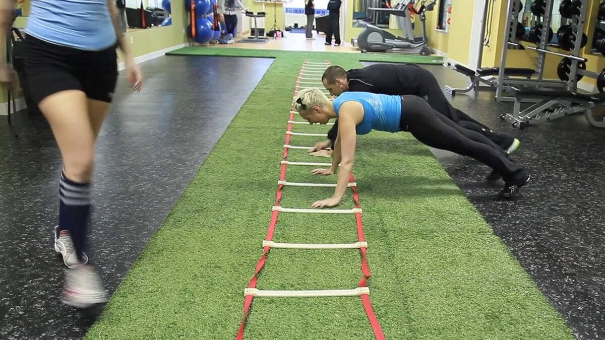 Club member Casie Stewart and Jason Cappellano, co-owner of the Motion Room, work their arms on the agility ladder