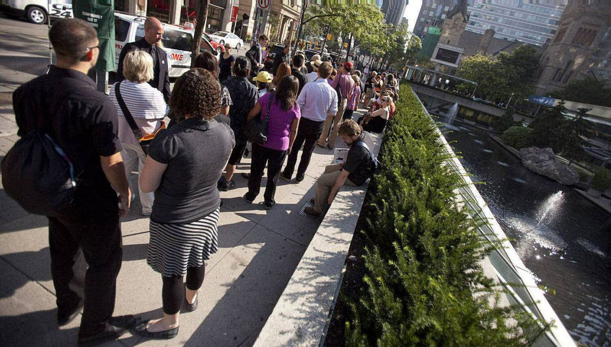 Hundreds of people que outside Roy Thomson Hall August 27, 2011, to obtain tickets for the state funeral for Mr. Layton.