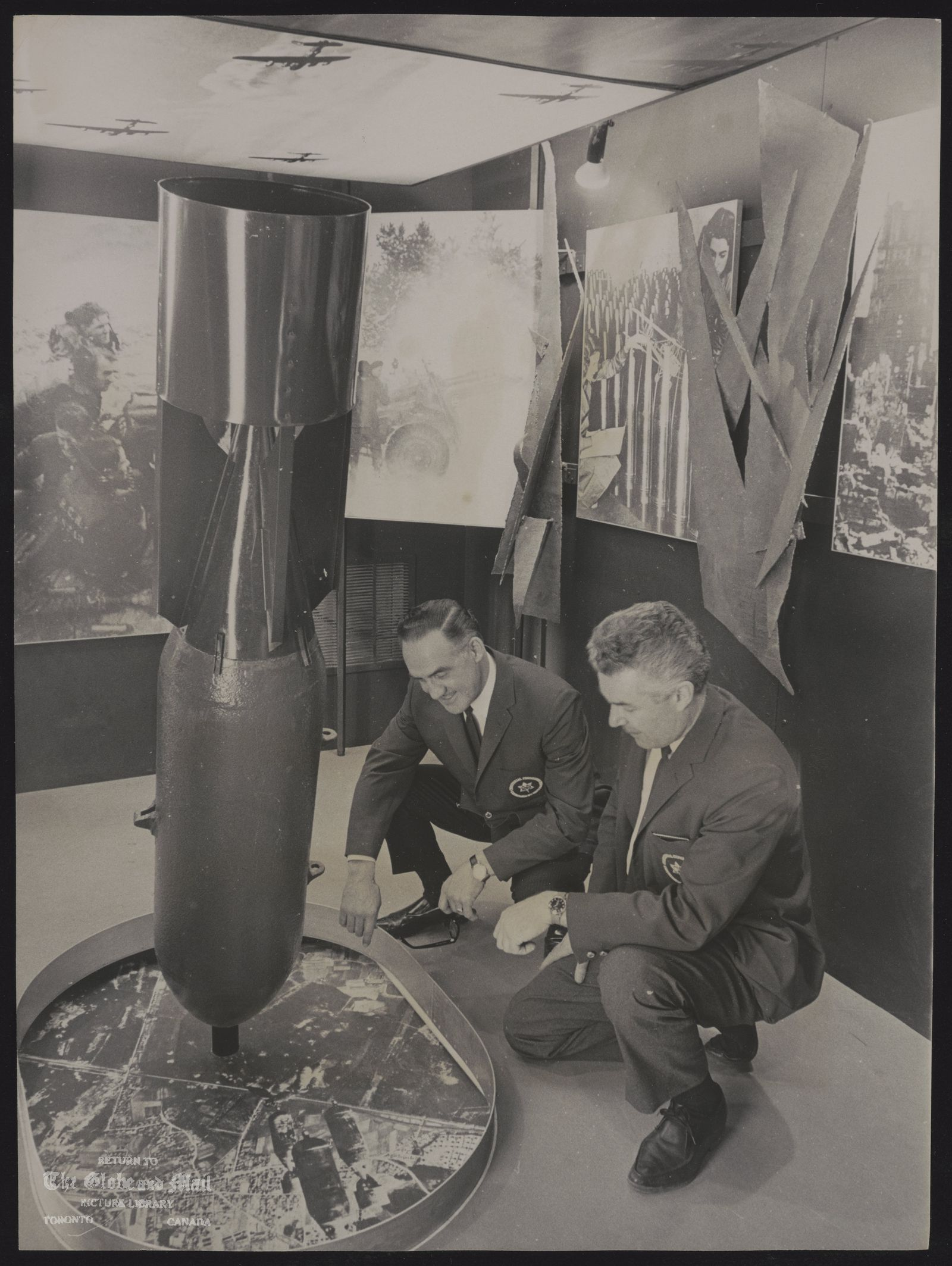 CANADA dominion Centennial Caravans Picture IV Caravan head John Coupland, right, and one of eight caravan managers John Bourbonnais look over 500-pound semi-armor piercing shell used in World War II. Both men are veteran fighter pilots with the RCAF. The bomb is part of the caravans' ward display.