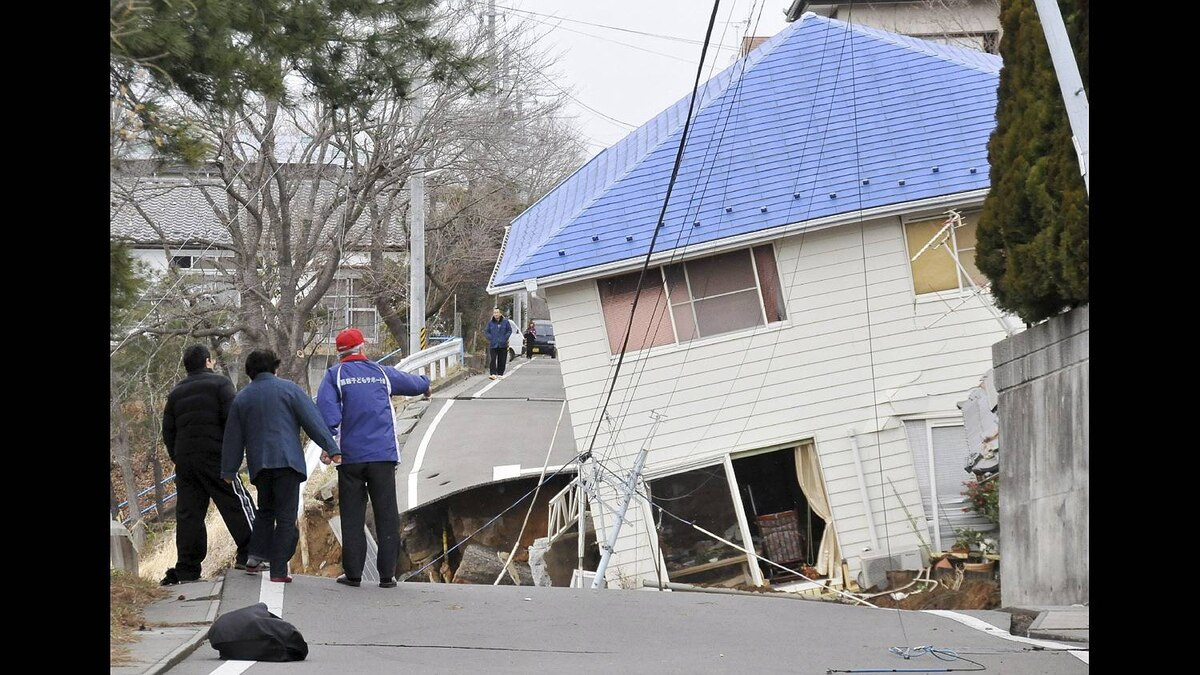 Residents check the damage done to a road house in Sukagawa city, Fukushima prefecture, in northern Japan on March 11, 2011.