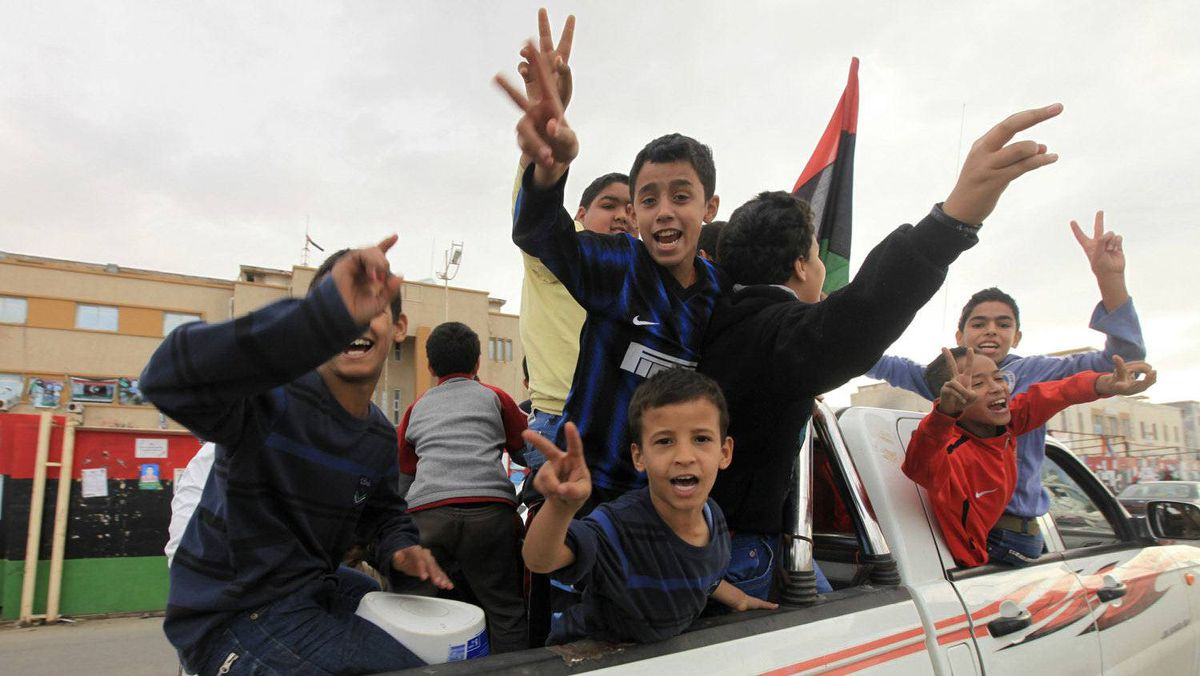 Children celebrate after hearing news of the arrest of Saif al-Islam Gaddafi, in Benghazi November 19, 2011. A spokesman for Libya's outgoing interim government said on Saturday that Saif al-Islam Gaddafi would be tried in the country rather than being sent to The Hague.