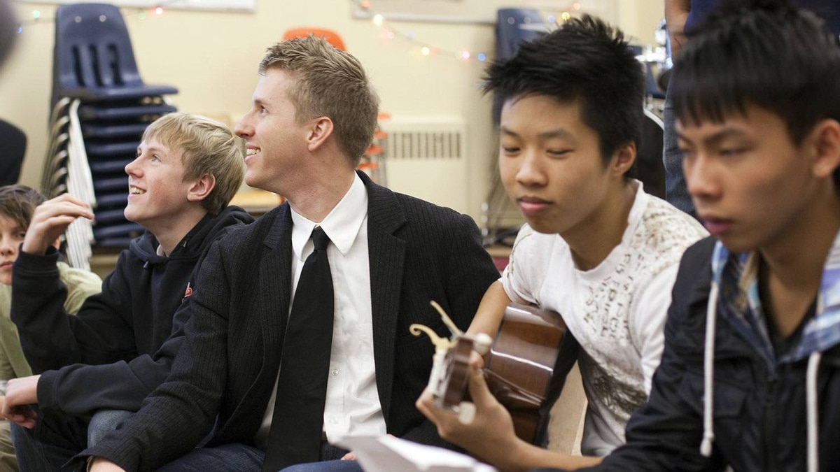 Teacher Mike Cavaletto talks with students from Sir Charles Tupper secondary school in Vancouver, British Columbia December 15, 2011.