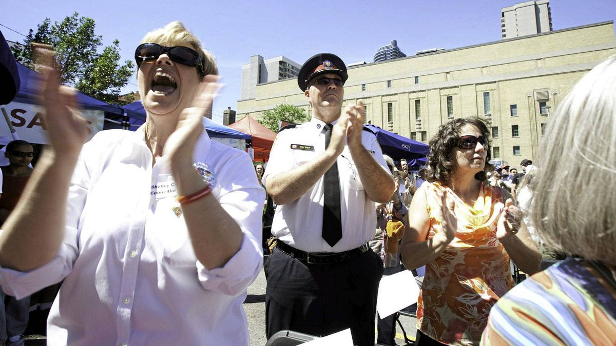 "Toronto City Councillor Shelley Carroll, left, and Toronto Police Chief Bill Blair with his wife Susanne, centre, sing along during ""Church on Church,"" the Metropolitan Community Church of Toronto's outdoor service."
