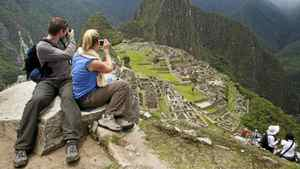 A tourist couple takes pictures of Inca's citadel of Machu Picchu in Cuzco.
