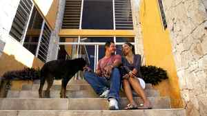 Joel Khawly and wife Sheila manage phone calls while posing for a photo outside the home they built in Jacmel.