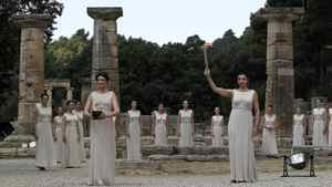 Having lit the torch from the Olympic flame, the high priestess raises the torch in front of the Hera temple alongside another priestess carrying a lit pot.