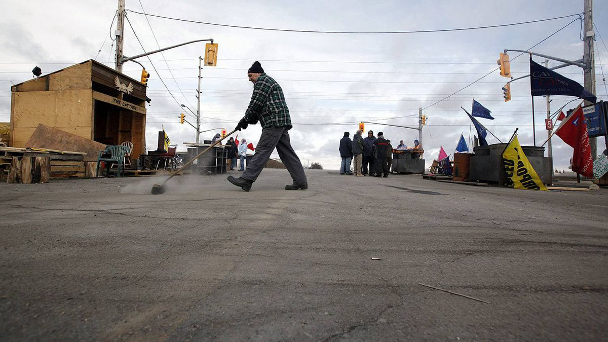 Electro-Motive Canada employee Edward Swat, 62, keeps himself busy sweeping the driveway on the picket line outside the subsidiary of Caterpillar in London on Feb. 8, 2012.