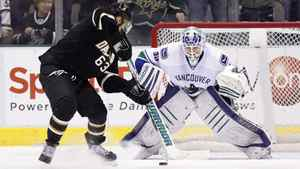 Vancouver Canucks goaltender Cory Schneider (R) eyes the puck as Dallas Stars center Mike Ribeiro prepares for a penalty shot during the second period of their NHL hockey game in Dallas, Texas March 22, 2012.