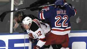 New Jersey Devils' Alexei Ponikarovsky (12) is checked along the boards by New York Rangers' Brian Boyle (22) during the first period of Game 1 of the NHL Eastern Conference Finals hockey playoffs at Madison Square Garden in New York, May 14, 2012. REUTERS/Ray Stubblebine