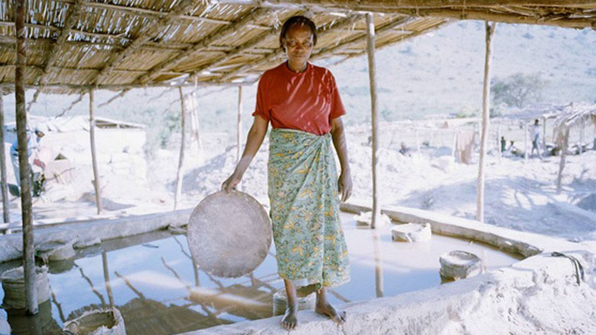 An artisan miner with her panning dish in which mercury and water are used to seperate gold dust deposit from ground rock.