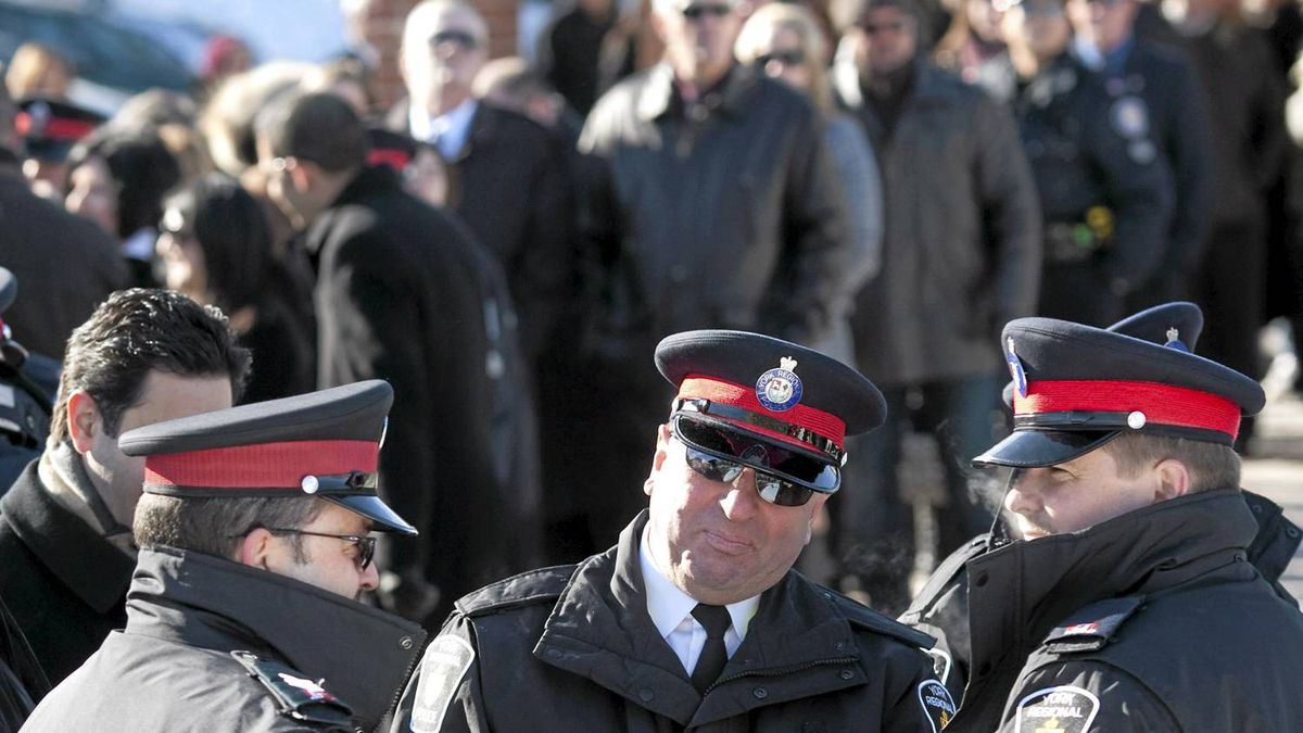 Police Officers wait in line at a funeral home in Toronto on Sunday January 16, 2011, as they wait to pay their respects to Sergeant Ryan Russell. Sgt. Russell was killed after trying to stop a man driving a stolen snowplow through the city early Wednesday morning, striking vehicles and nearly hitting people.