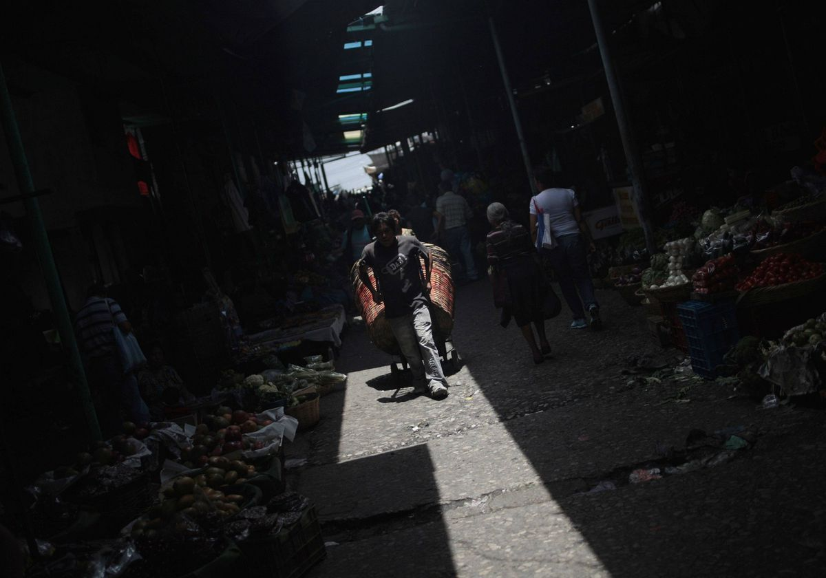 A man drags a cart along a corridor of the La Terminal food market in Guatemala City. La Terminal is one of the largest trading centres in the city, with more than 4,500 vendors offering a wide variety of food products, according to Guatemalan authorities.