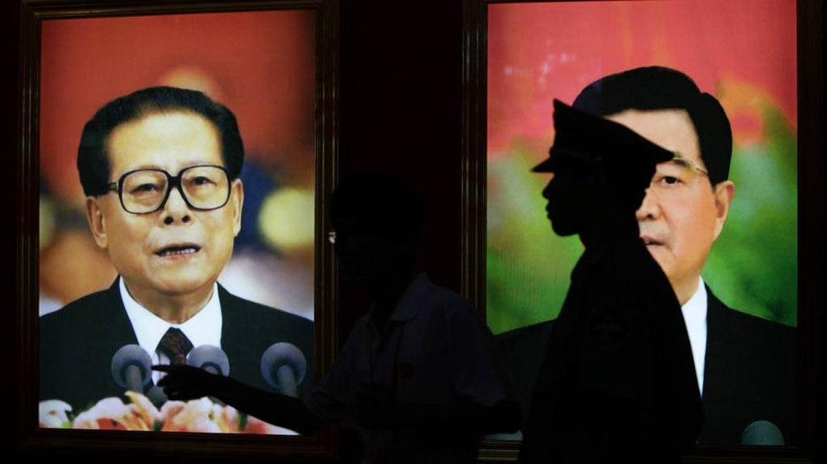 A security guard stands next to pictures of China's former President Jiang Zemin (L) and President Hu Jintao at an exhibition to celebrate the 90th anniversary of the founding of the Communist Party of China (CPC) in Beijing July 7, 2011.