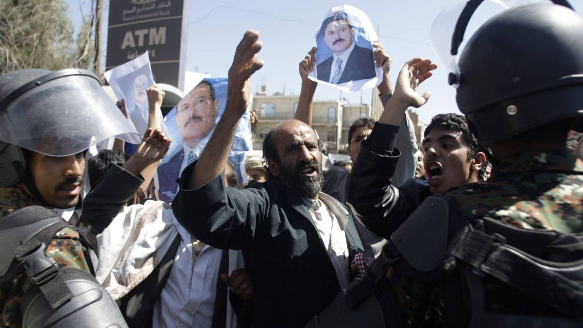 Anti-riot policemen block government supporters shouting at opposition supporters during an anti-government rally outside Snaa University campus in Sanaa January 22, 2011.