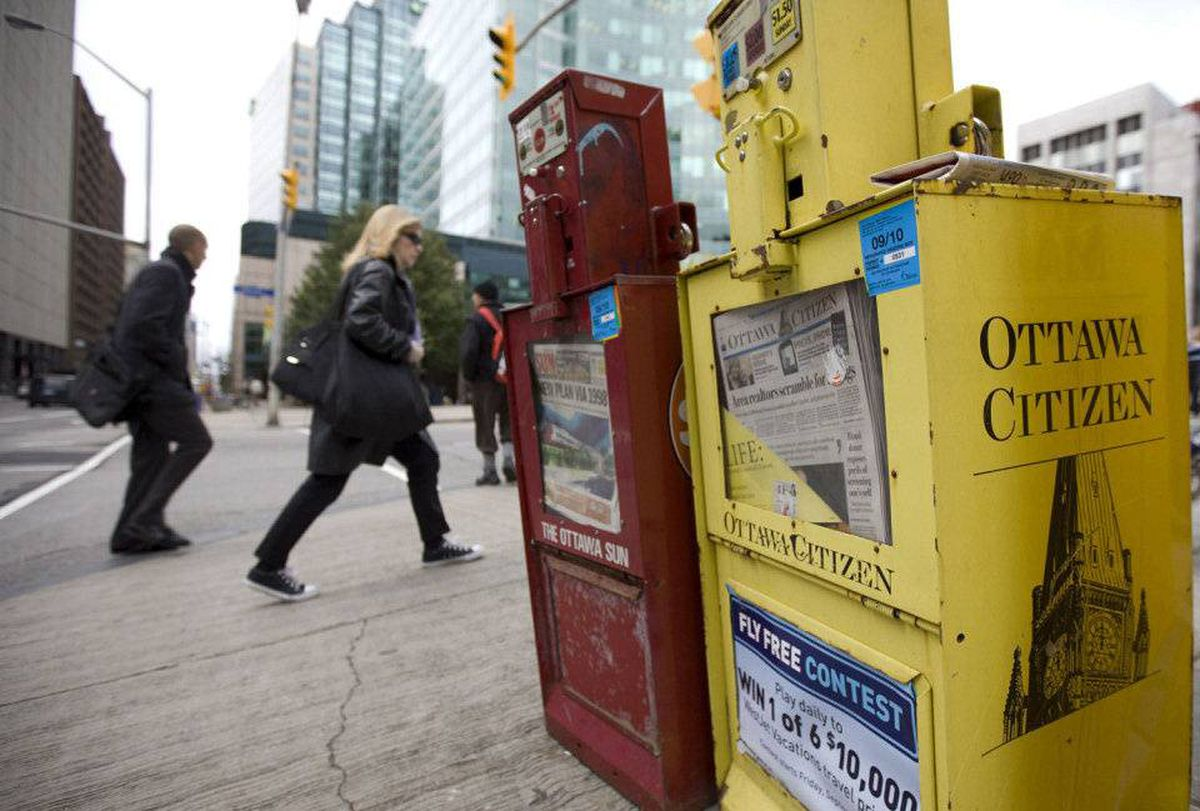 Pedestrians walk past a Ottawa Citizen newspaper box in downtown Ottawa.