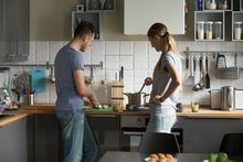 Young man and woman, couple cooking healthy meal  together in kitchen, talking, wife stirring soup in saucepan on kitchen stove, husband cutting apples, household duties, family spending time together