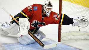 Calgary Flames goalie Miikka Kiprusoff, from Finland, dives across the crease to try and stop a goal during second period pre-season NHL hockey action in Calgary, Alta., Sunday, Sept. 25, 2011.THE CANADIAN PRESS/Jeff McIntosh