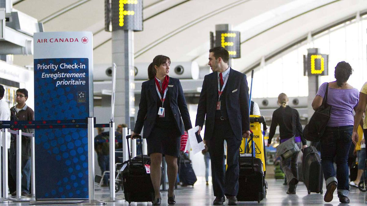 Air Canada flight attendants walk to the departures gate at Toronto Pearson airport on Oct. 10, 2011.